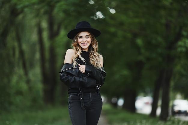 革のジャケットと夏の街で一人で歩いて黒い帽子の若い女性の肖像画