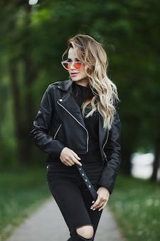 革のジャケットとファッショナブルなサングラスの若い女性は夏の日の屋外で一人で歩いています。