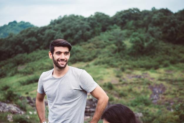 Красивый мужчина стоит и смотрит на природу, счастливый и улыбающийся, позитивное мышление, путешествие на природе