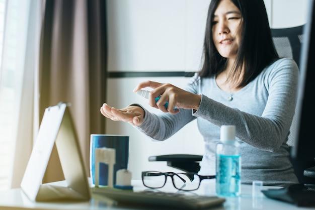 Азиатские руки женщины используют дезинфицирующий гель в аэрозольном баллончике для защиты рук от коронавируса