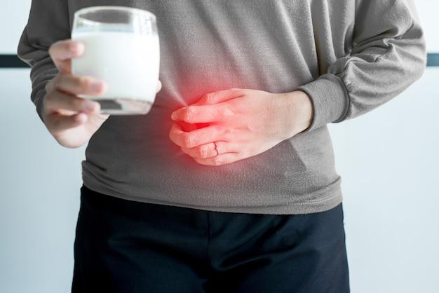 ミルクのガラスと胃の痛みを持つアジアの女性