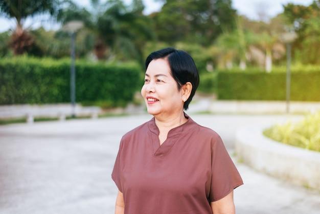 Портрет зрелой азиатской женщины стоя на общественном парке, счастливый и усмехаясь, концепция страхования старшей заботы