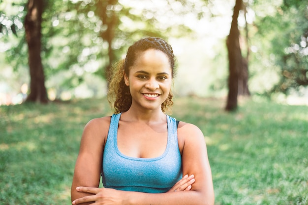 Привлекательная негритянка улыбается, эмоционально позирует после тренировки на улице, позитивное мышление и улыбка, время отдыха