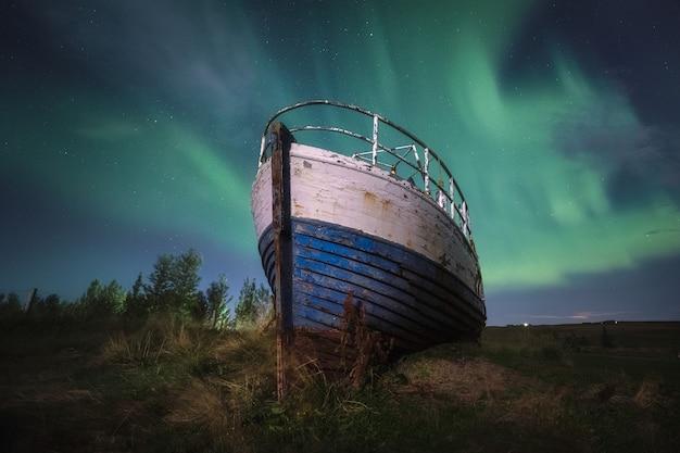 アイスランドの放棄された船のオーロラ。