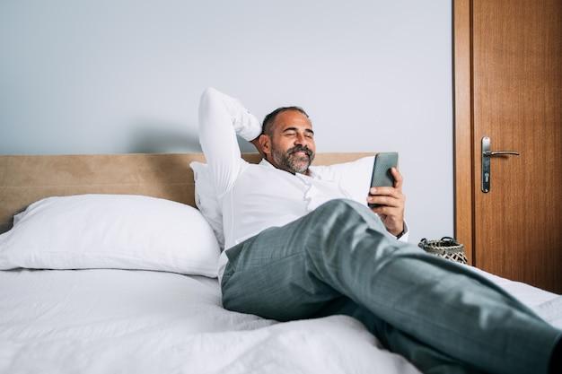 携帯電話を見てベッドに横たわってリラックスした実業家
