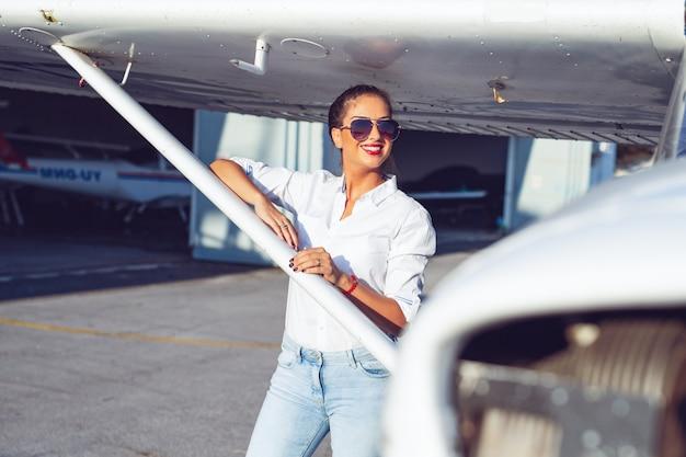 Красивая женщина-пилот в ангаре делает предполетную подготовку