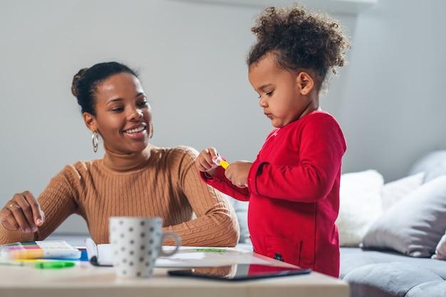 Счастливая мать афроамериканцев, помогая своей дочери в окраске