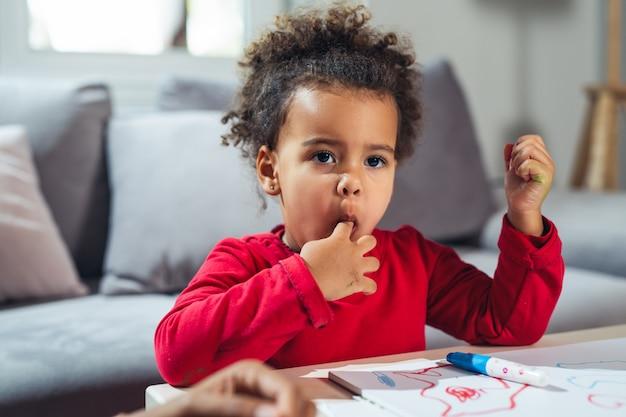Маленькая девочка ест конфеты в домашних условиях