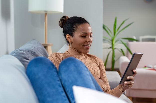 Красивая молодая женщина улыбается и смотрит на планшет