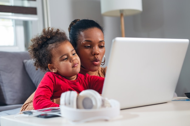 Афро-американская мать с маленькой дочерью, используя ноутбук вместе