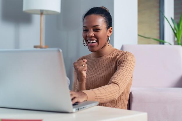 Красивая молодая женщина улыбается и смотрит на экран ноутбука