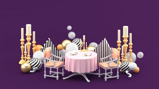 紫色のスペースにカラフルなボールの中でディナーテーブルとキャンドルホルダー