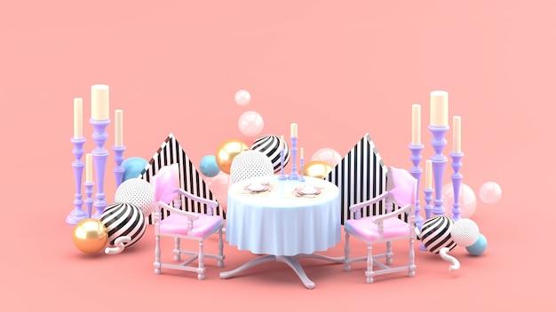 Обеденный стол и подсвечник среди разноцветных шариков на розовом пространстве