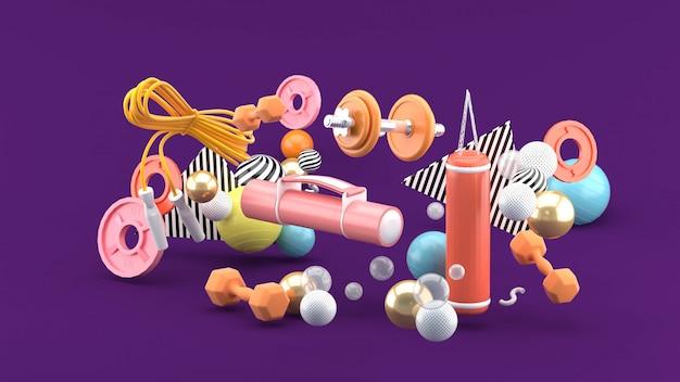 Фитнес оборудование среди разноцветных шариков на фиолетовом пространстве