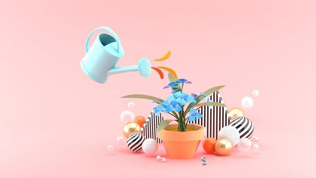 シャワーはピンクのスペースにあるカラフルなボールの中で花に水を注いだ