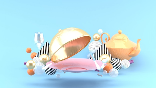Золотая крышка от еды, тарелка, бокал и чайник в окружении разноцветных шариков на голубом пространстве