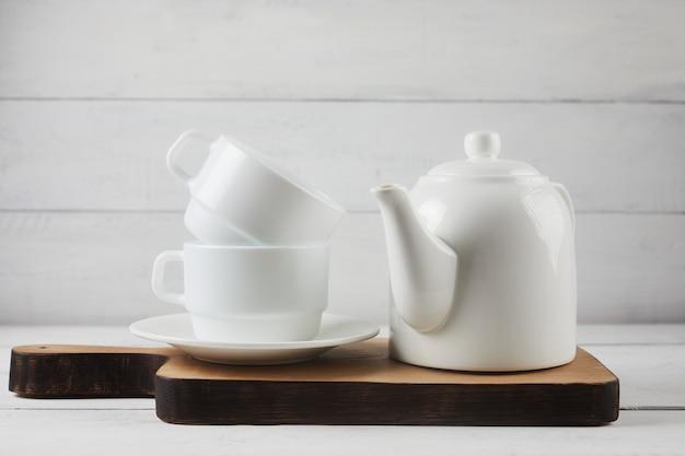 Чашка чая, чайник, дубовая разделочная доска на белом