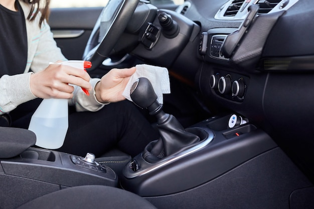 車を消毒するための消毒剤と消毒ウェットワイプを噴霧する女性の手