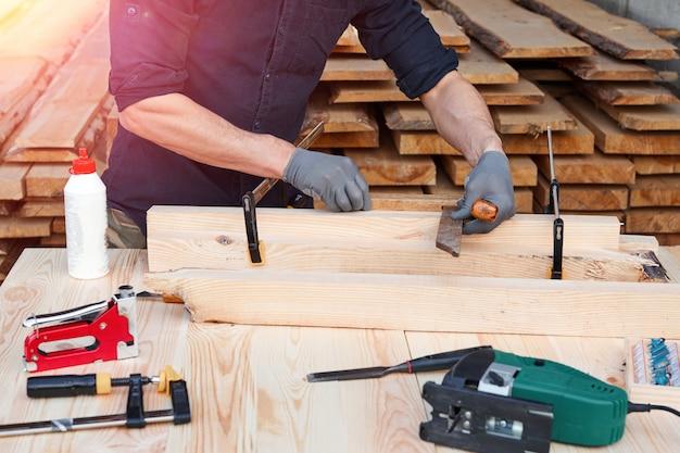Плотник работая с самолетом на деревянной предпосылке