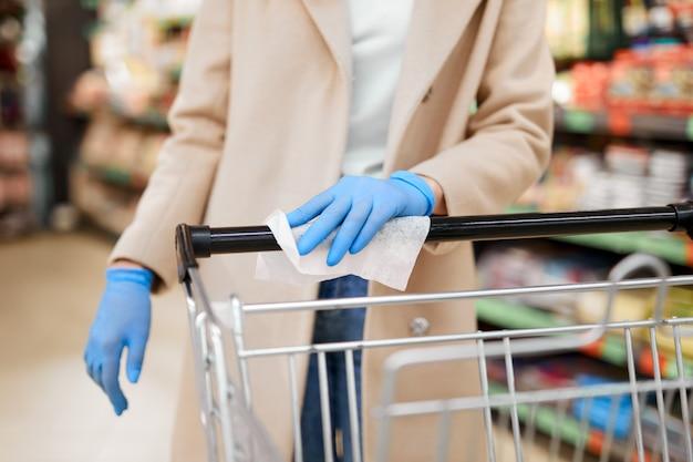 保護手袋を持つ女性は、スーパーマーケットで消毒布でショッピングカートのハンドルを拭きます。コロナウイルスのパンデミック時の安全性。