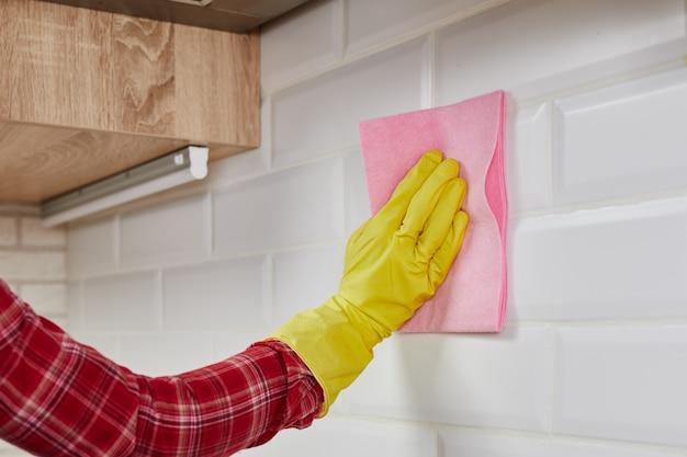 ピンクの布と手袋でキッチンタイルを掃除する女性。家庭用機器、片付け、クリーニングサービスのコンセプト。