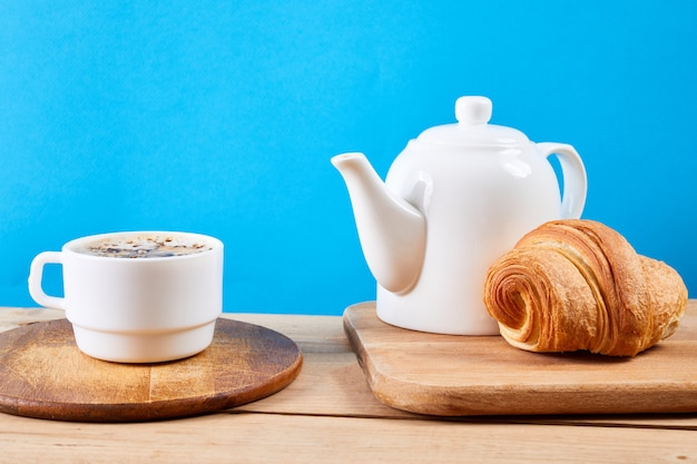 クロワッサンと朝食。新鮮なクリスピークロワッサンとコーヒーと木製のテーブル