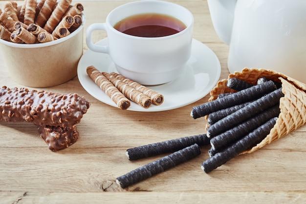 ワッフルロールとチョコレートのお菓子、木製の背景、上面にお茶とワッフルコーン