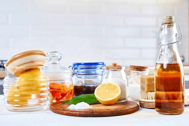 Экологичные натуральные чистящие средства: пищевая сода, мыло, уксус, соль, кофе, лимон и кисточка на деревянном столе