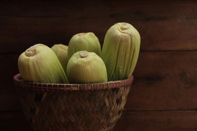 木製の背景に竹ご飯かごのトウモロコシ