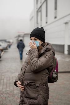 Беременная женщина стоит на улице европейского города во время эпидемии коронавируса.