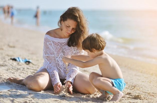 Мама с ребенком сидит на пляже и играет в песок летом