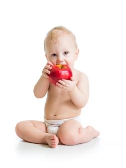 Мальчик ест красное яблоко, изолированное на белом