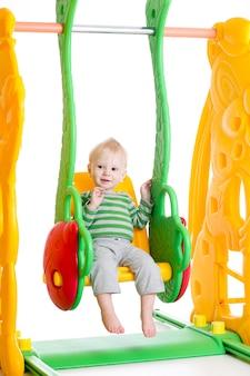 幼児のブランコで遊ぶ少年