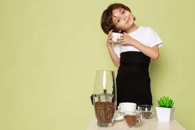 Вид спереди улыбающегося милого мальчика в белой футболке возле стола с кофе на каменном столе