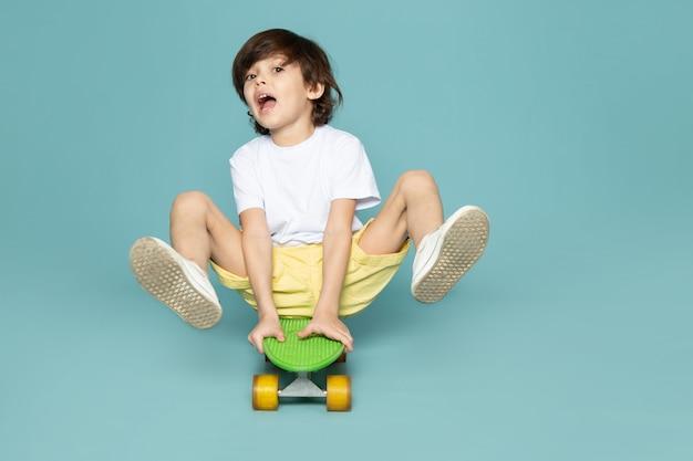 Вид спереди маленького мальчика в белой футболке и желтых джинсах на зеленом скейтборде на синем полу