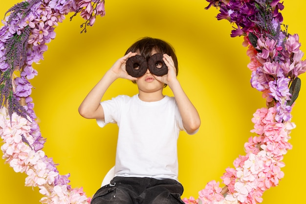 Вид спереди милый мальчик с шоколадными пончиками в белой футболке на желтом пространстве