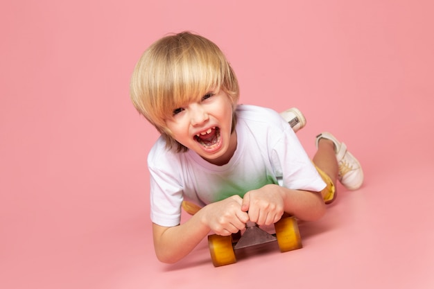Вид спереди, кричащий белокурый мальчик на зеленом скейтборде на розовом полу