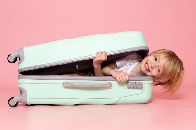 Вид спереди улыбающегося белокурого мальчика в белой сумке на розовом полу