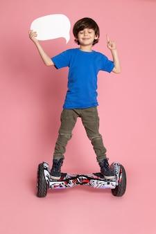 Улыбающийся мальчик спереди в синей футболке и брюках цвета хаки, едущий на сегвее на розовом полу