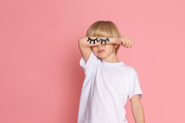 Вид спереди малыш в белой футболке с руками закрыл глаза на розовом столе