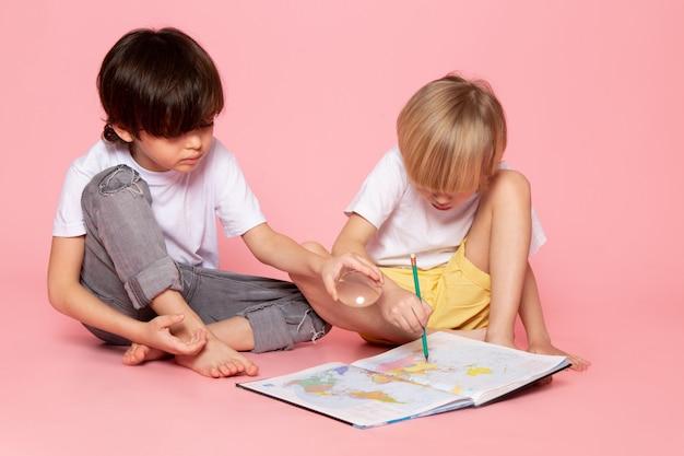 Вид спереди два мальчика в белых футболках рисуют карту на розовом