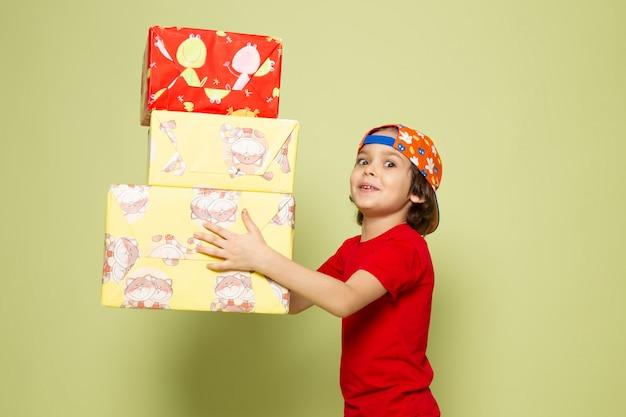 Вид спереди милый мальчик в красной майке держит подарки на каменном цветном пространстве