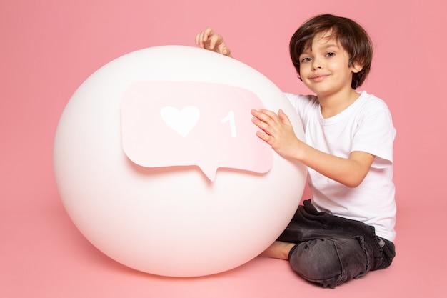 Вид спереди улыбающегося милого мальчика в белой футболке, играющего с белым круглым шариком на розовом пространстве