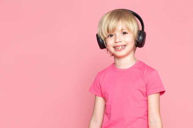 Маленький мальчик в розовой футболке и черных наушниках слушает музыку