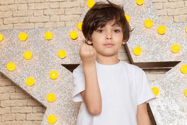 Вид спереди милый маленький ребенок в белой футболке темных джинсах на звездочке разработан желтый стенд и светлый фон