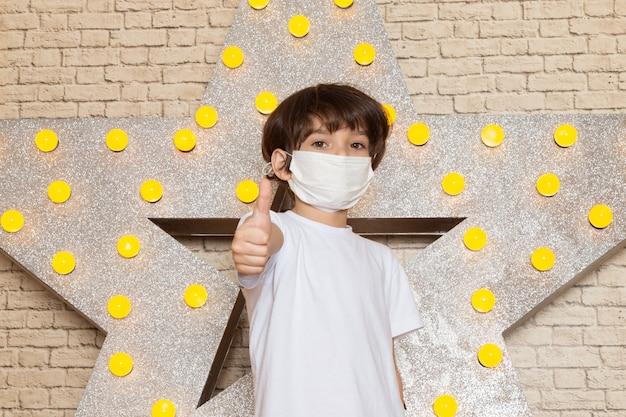 Вид спереди милый маленький ребенок в белой футболке, темных джинсах, белой стерильной маске на звездочке с желтым дизайном и светлом фоне