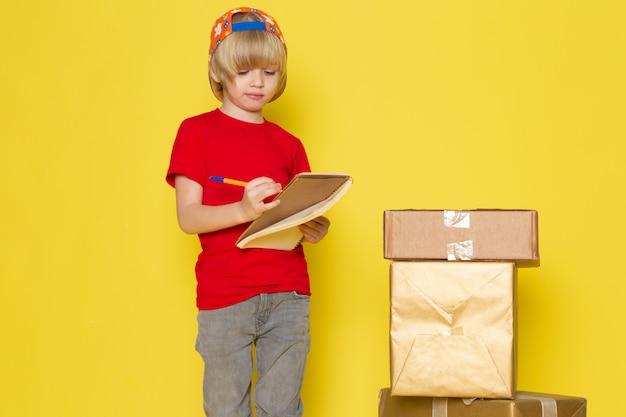 Вид спереди маленький мальчик в красной футболке красочной шапке и серых джинсах держит коробку на желтом фоне