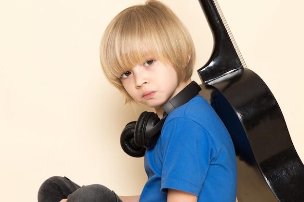 Вид спереди крупным планом милый маленький мальчик в синей футболке с черными наушниками держит черную гитару