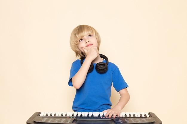 Вид спереди милый маленький мальчик в синей футболке с черными наушниками, играя маленькую милую позу мышления фортепиано