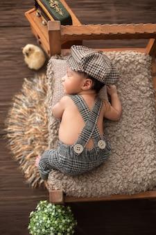 Новорожденный маленький симпатичный мальчик лежит на деревянной кровати в детском костюме и шляпе